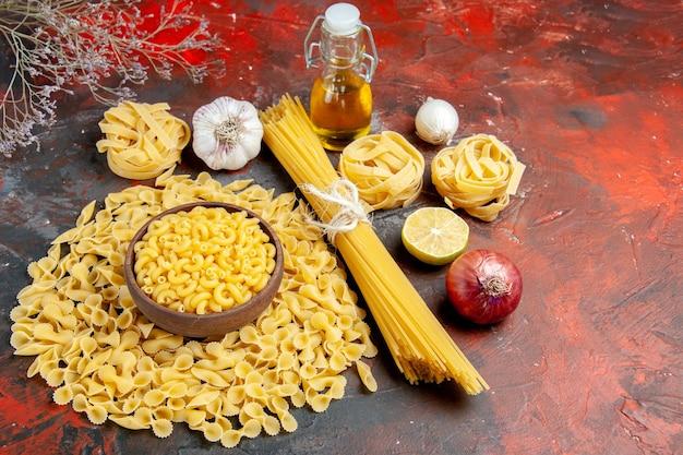 Zijaanzicht van ongekookte pasta's in verschillende vormen, knoflook en uienoliefles op gemengde kleurentafel