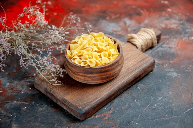 Zijaanzicht van ongekookte pasta's op houten snijplank op gemengde kleurentafel