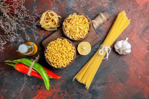 Zijaanzicht van ongekookte pasta's op snijplank cayennepeper in elkaar gebonden met touw olie fles citroen of knoflook op gemengde kleur tabelmateriaal