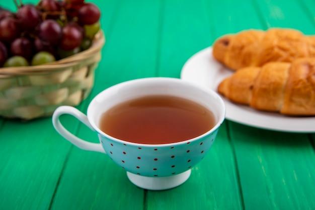 Zijaanzicht van ontbijt dat met croissants in plaatkop thee en mand van de bessen van de druivensleeprijs op groene achtergrond wordt geplaatst