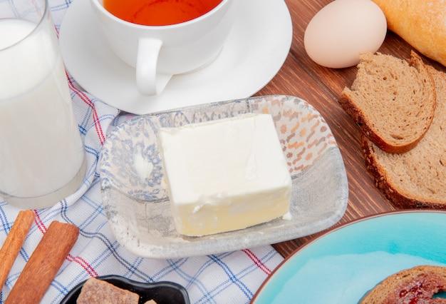 Zijaanzicht van ontbijt set met boter rogge sneetjes brood besmeerd met jam in plaat melk kaneel thee op geruite doek en houten tafel