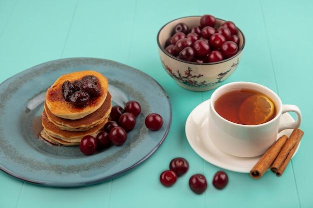 Zijaanzicht van ontbijtset met kopje thee en kaneel op schotel en pannenkoeken met kersen in plaat en kom met kersen op blauwe achtergrond