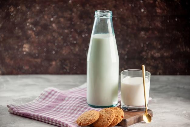 Zijaanzicht van open glazen fles en beker gevuld met melkkoekjes op paarse gestripte handdoek op houten snijplank