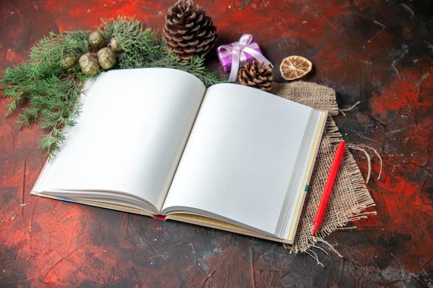 Zijaanzicht van open spiraalvormig notitieboekje met rode pen en dennentakken op handdoek op donkere achtergrond