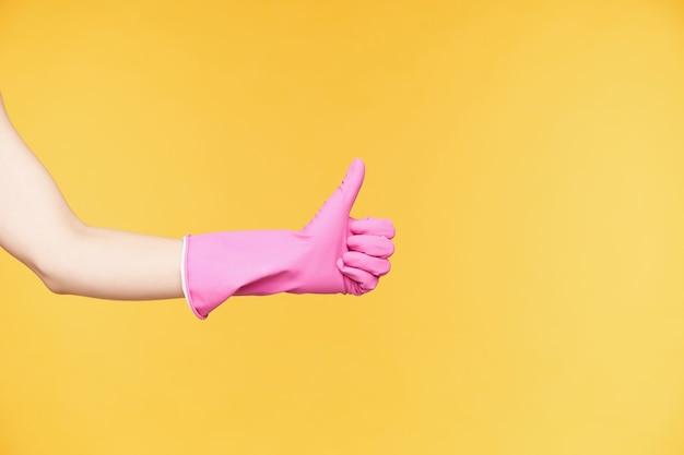 Zijaanzicht van opgeheven hand in rubberen handschoenen beduimelt omhoog terwijl het tonen van positieve emoties, tevreden zijn tijdens het beëindigen van de voorjaarsschoonmaak, geïsoleerd op oranje achtergrond