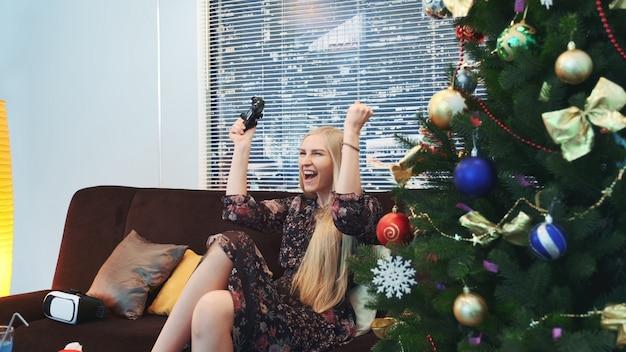 Zijaanzicht van opgewekte dame die een videospelletje op console wint op kerstmis