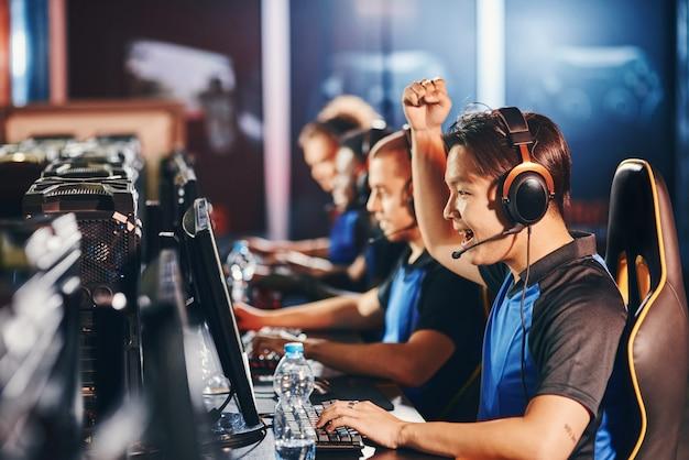 Zijaanzicht van opgewonden jonge aziatische man mannelijke cyber sport gamer kijken naar pc-scherm