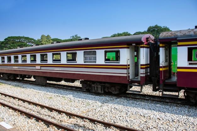 Zijaanzicht van oude passagierstrein die zich door station bij de zomer beweegt