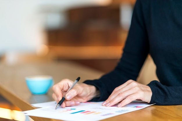 Zijaanzicht van oudere bedrijfsvrouw die met documenten werkt