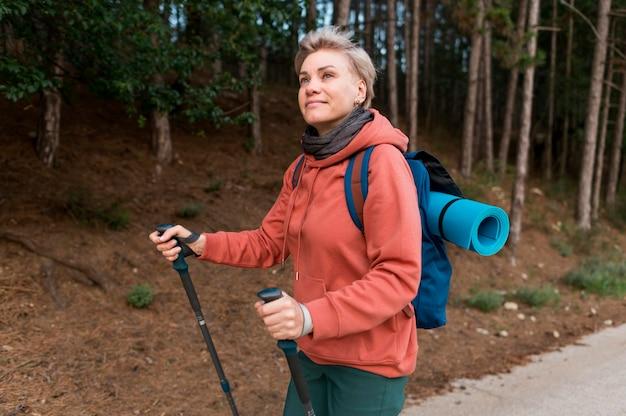 Zijaanzicht van oudere toeristenvrouw in het bos met wandelstokken