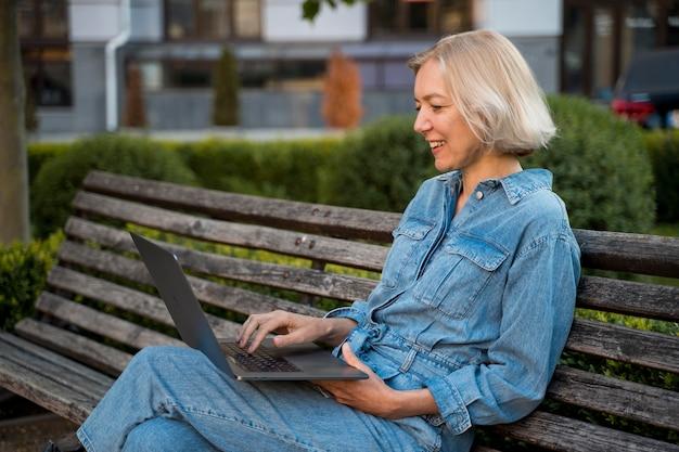 Zijaanzicht van oudere vrouw buiten op bankje met laptop