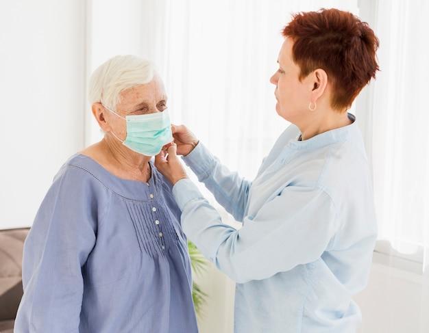 Zijaanzicht van oudere vrouw die medisch masker op een andere oudere vrouw zet