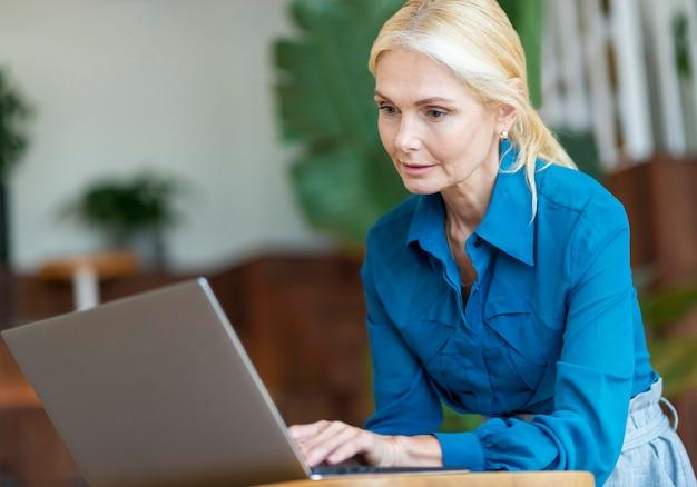 Zijaanzicht van oudere vrouw die op laptop werkt terwijl uit