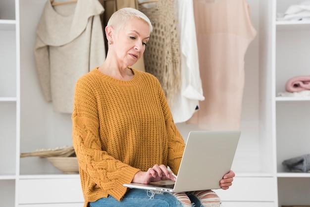 Zijaanzicht van oudere vrouw die op laptop werkt
