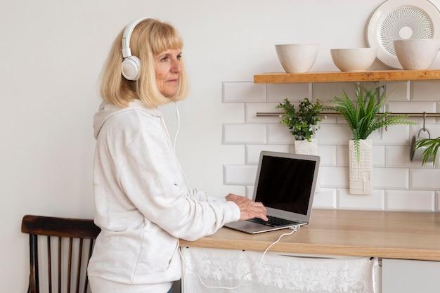 Zijaanzicht van oudere vrouw, luisteren naar muziek op de koptelefoon thuis met laptop