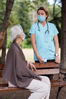 Zijaanzicht van oudere vrouw met medisch masker bij verpleeghuis met vrouwelijke verpleegster