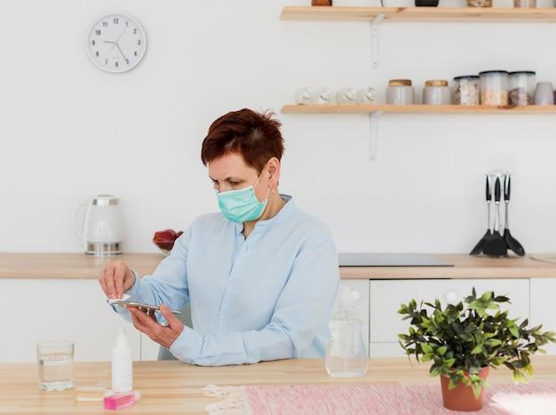 Zijaanzicht van oudere vrouw met medisch masker dat haar smartphone desinfecteert