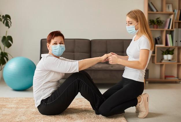 Zijaanzicht van oudere vrouw met medisch masker in covidherstel die fysieke oefeningen doet