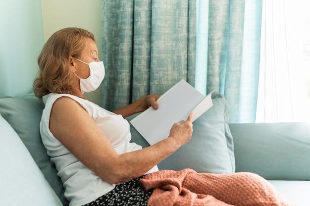 Zijaanzicht van oudere vrouw met medisch masker thuis tijdens de pandemie die een boek leest