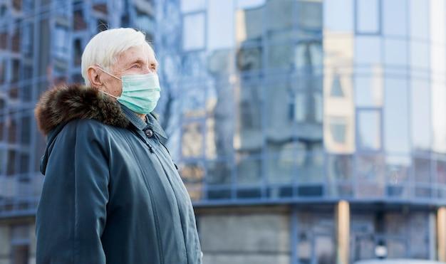 Zijaanzicht van oudere vrouw met medische masker in de stad