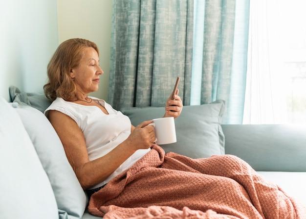 Zijaanzicht van oudere vrouw thuis tijdens de pandemie, genietend van een kopje koffie en het gebruik van smartphone