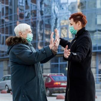 Zijaanzicht van oudere vrouwen die elkaar in de stad begroeten