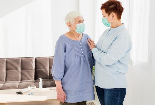 Zijaanzicht van oudere vrouwen die thuis medische maskers dragen