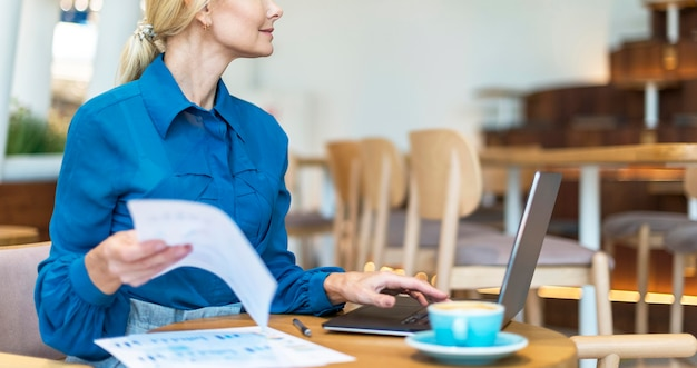 Zijaanzicht van oudere zakenvrouw die op laptop werkt terwijl het hebben van een kopje koffie