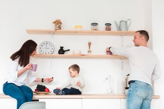Zijaanzicht van ouders met kind in de keuken