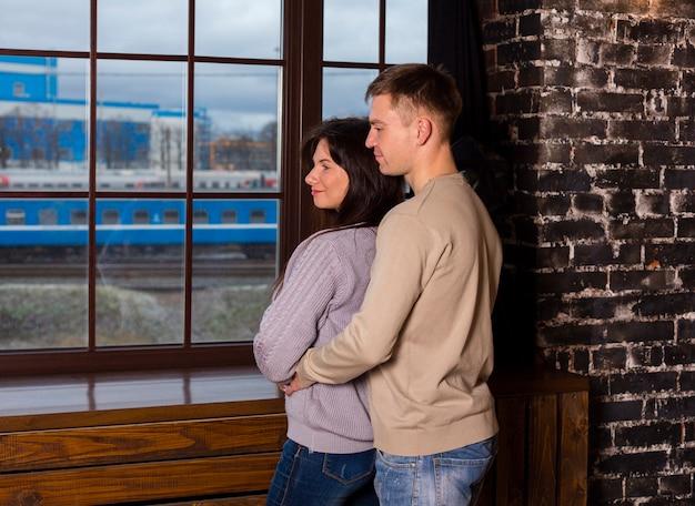 Zijaanzicht van paar dat door venster kijkt terwijl omhelst