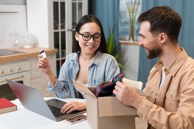 Zijaanzicht van paar dat geniet van de online bestelling die ze hebben ontvangen
