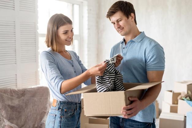 Zijaanzicht van paar die kleren inpakken om te verhuizen