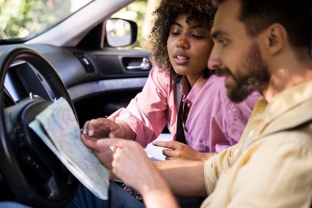 Zijaanzicht van paar in auto raadplegingskaart