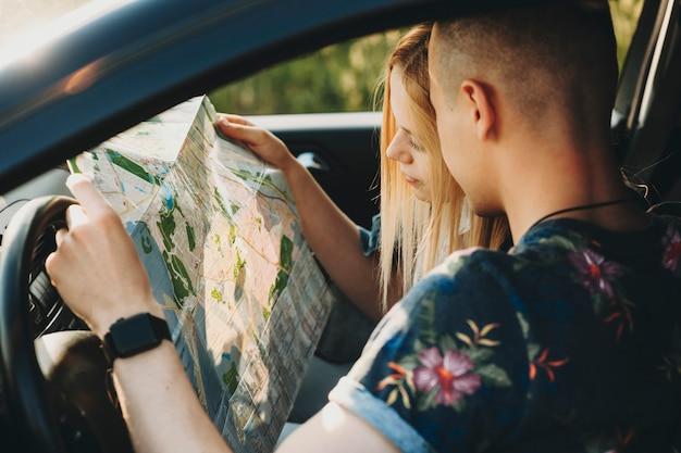 Zijaanzicht van paar in auto zitten en navigeren met papieren kaart