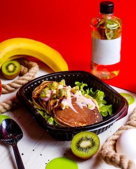Zijaanzicht van pannenkoeken geserveerd met yoghurt en kiwi in levering doos