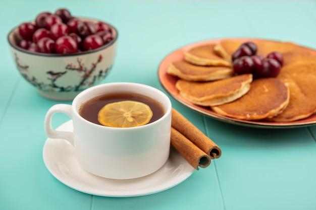 Zijaanzicht van pannenkoeken met kersen in plaat en kopje thee met schijfje citroen erin en kaneel op schotel en kom met kersen op blauwe achtergrond