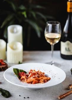 Zijaanzicht van pasta met tomatensaus en parmezaanse kaas in witte kom