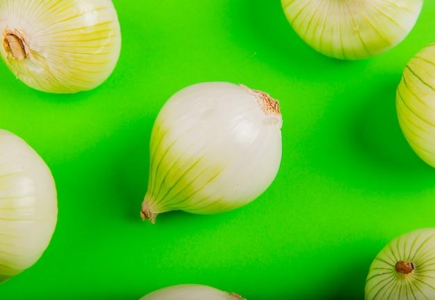 Zijaanzicht van patroon van uien op groene tafel