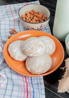 Zijaanzicht van peperkoek in plaat met amandelen op plaid doek en zure geklonterde melk op houten oppervlak