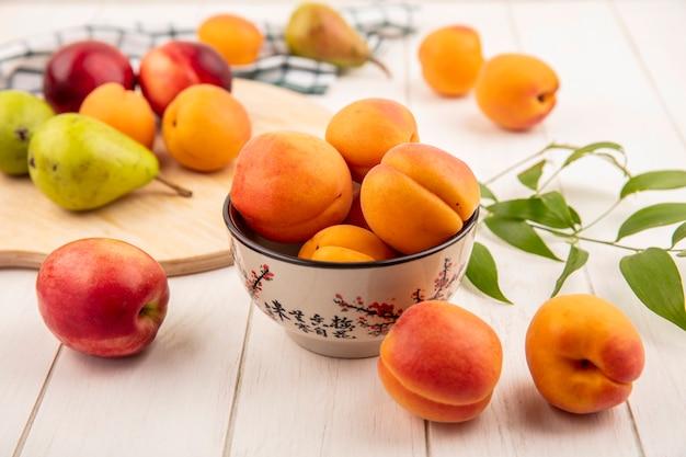 Zijaanzicht van perziken in kom en peren met perziken op snijplank en bladeren op houten achtergrond