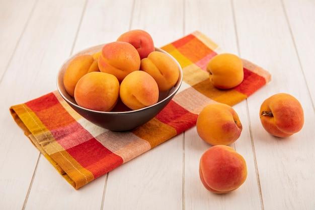 Zijaanzicht van perziken in kom op geruite doek en op houten achtergrond