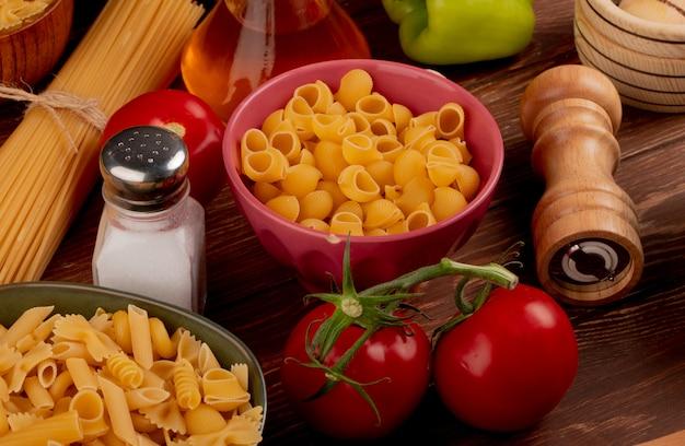 Zijaanzicht van pijp-rigate pasta in kom met andere soorten in een andere kom en zout tomatenboter peper op houten tafel