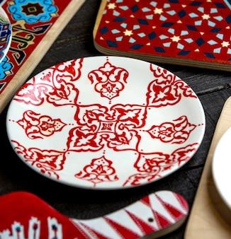 Zijaanzicht van plaat met ornamenten in rood