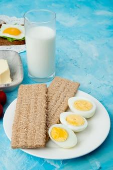 Zijaanzicht van plaat van knäckebroden en eieren met glas melk op blauwe achtergrond met exemplaarruimte
