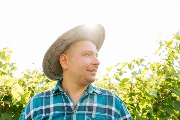 Zijaanzicht van portret van een wijnmaker met een hoed die in wijngaarden staat vrolijke boer in hemd met ...
