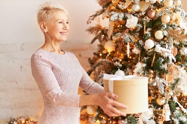 Zijaanzicht van positieve vrouw van middelbare leeftijd in een mooie jurk met kerstcadeaus. rijpe vrouw met blond kort haar die bij nieuwjaarsboom stellen, handen uitreiken, doos vasthouden en gelukkig glimlachen