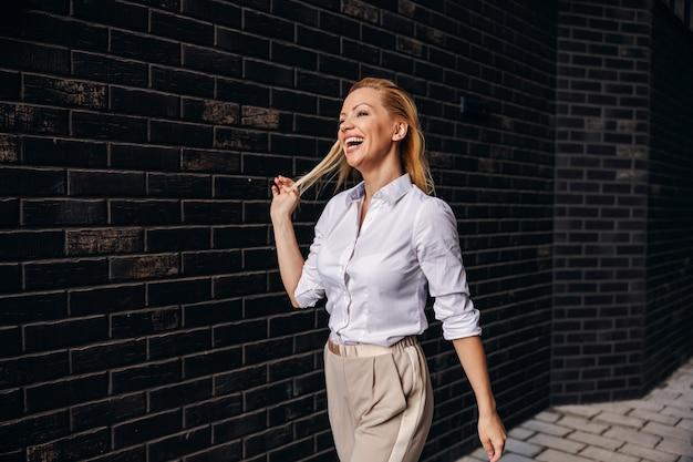Zijaanzicht van prachtige blonde modieuze zakenvrouw lopen op straat.