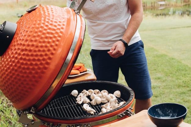 Zijaanzicht van proces om champignons bij de grill te roosteren