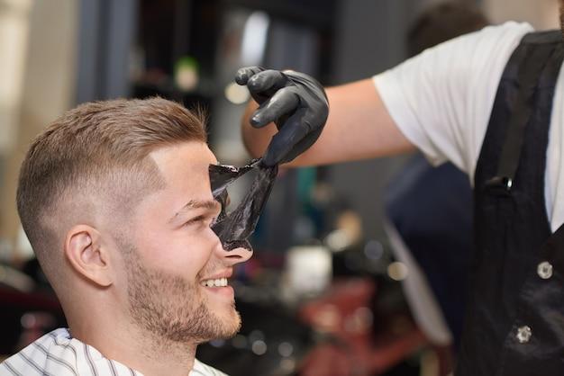 Zijaanzicht van proces om zwart masker van gezicht van de mens te verwijderen