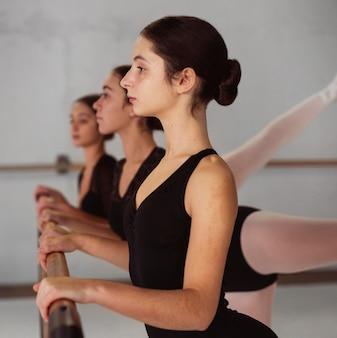 Zijaanzicht van professionele ballerina's die in maillots trainen